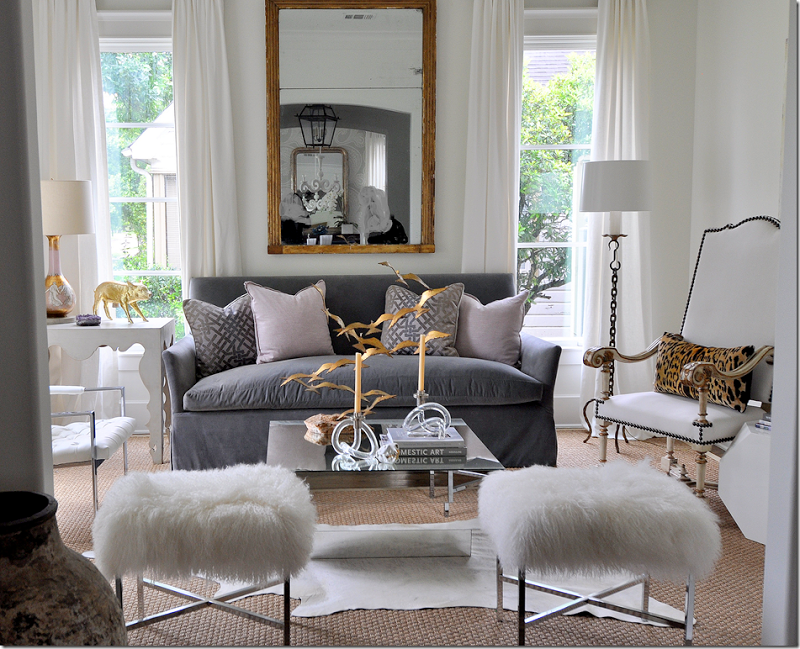 White Living Room with Gray Couch and Fur Stools