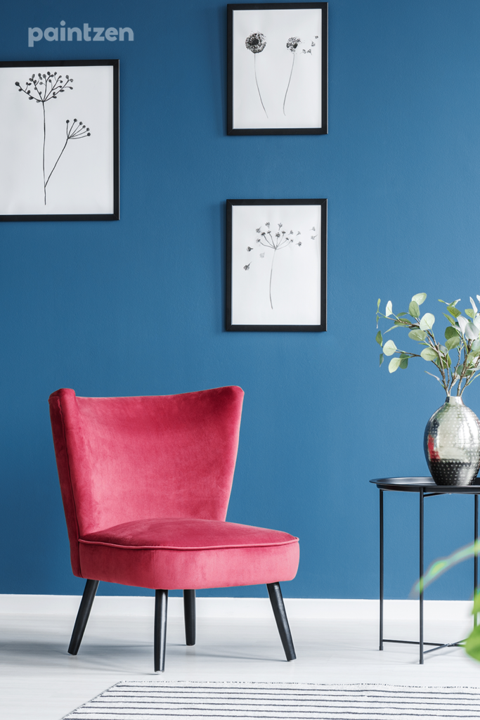 blue accent wall with red accent chair