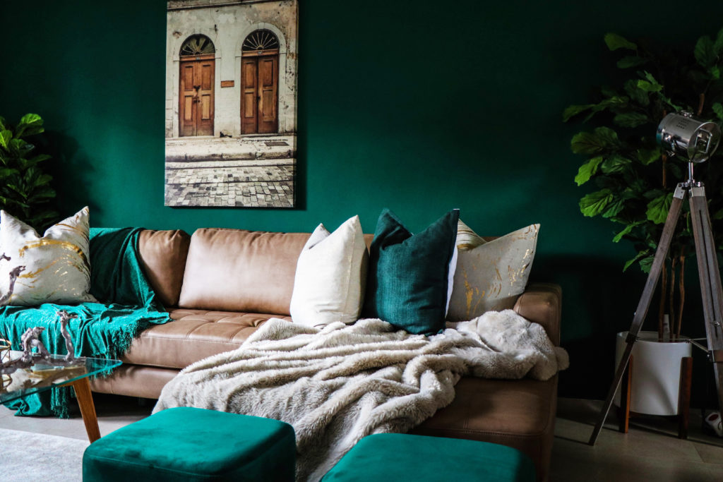 dark forest green living room with brown leather couch